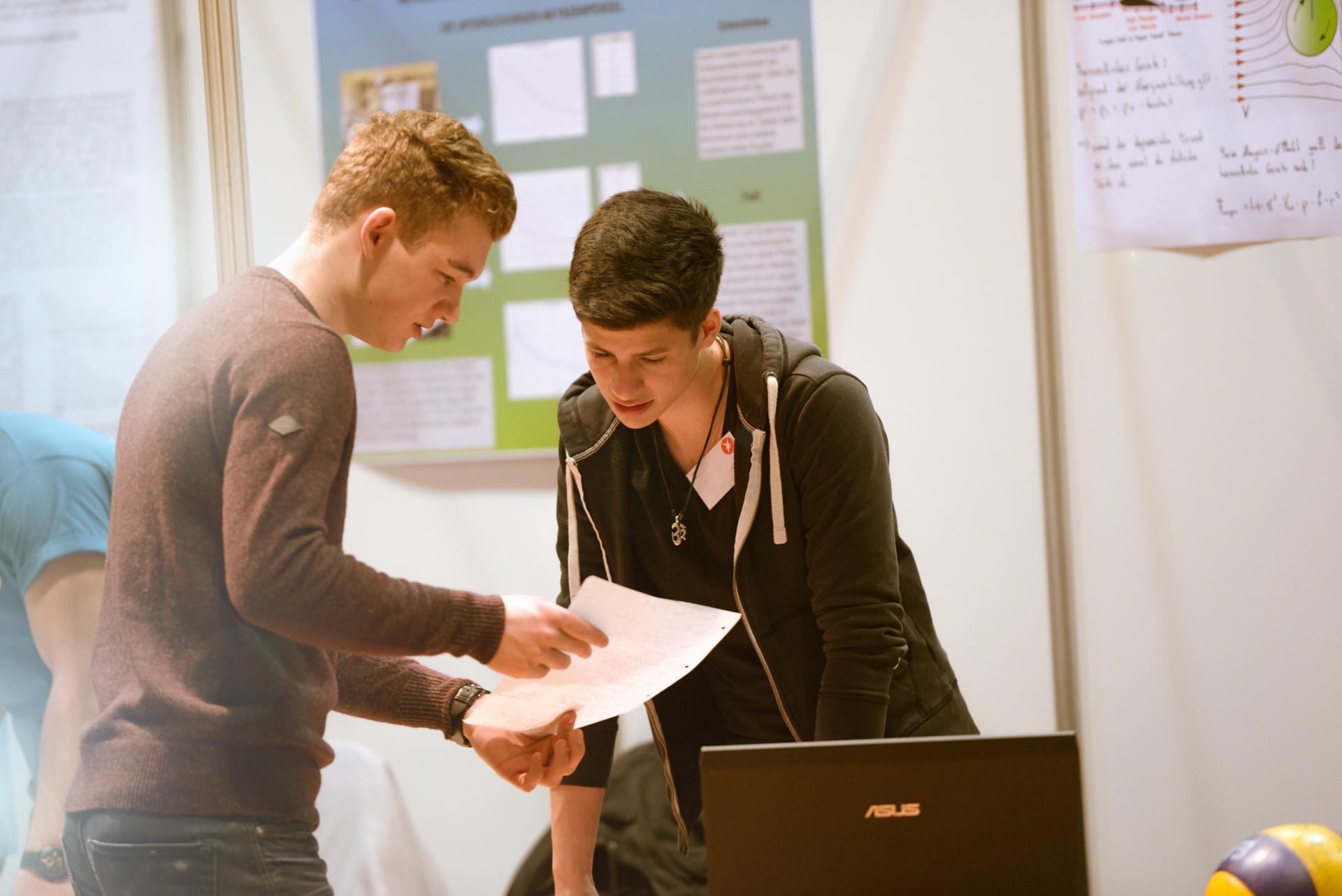 Zwei Schüler im Gespräch mit Zettel in der Hand