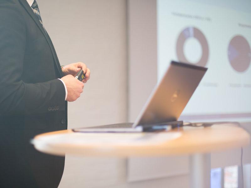 Mann mit Laptop bei Präsentation