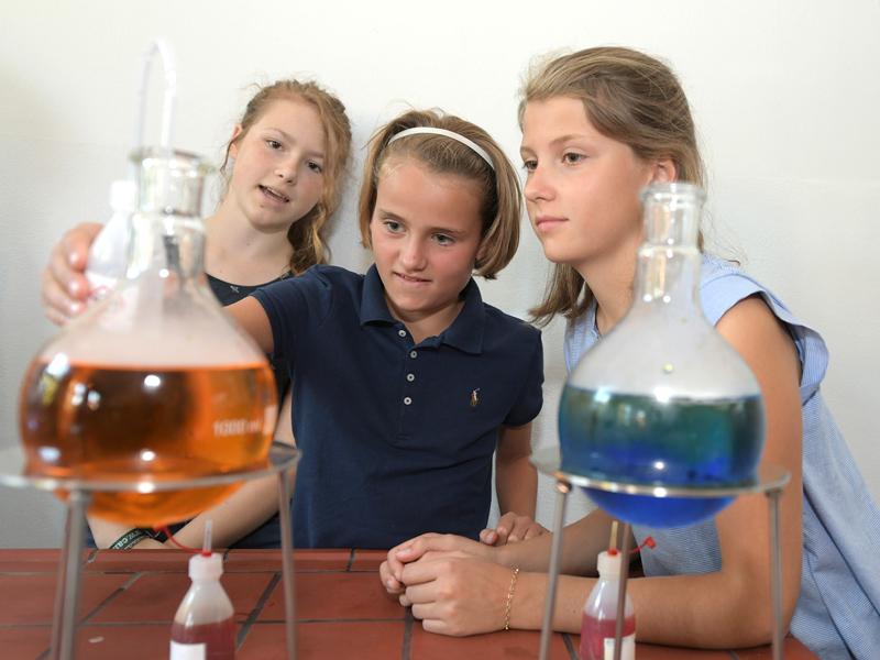 Drei Mädchen schauen einem Experiment zu