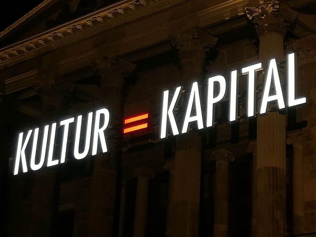 Leuchtschriftzug Kultur gleich Kapital an Gebäude