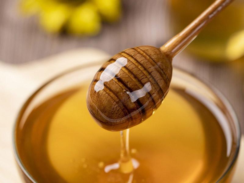 Honig fließt über einen Honiglöffel