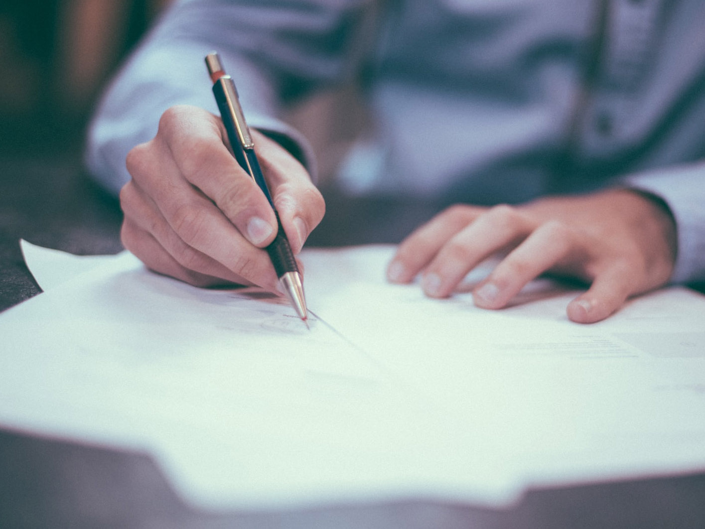 Mann schribt mit Stift auf weißem Papier