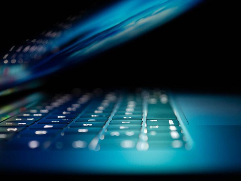 Laptop halb zusammen geklappt leuchtet im Dunkeln